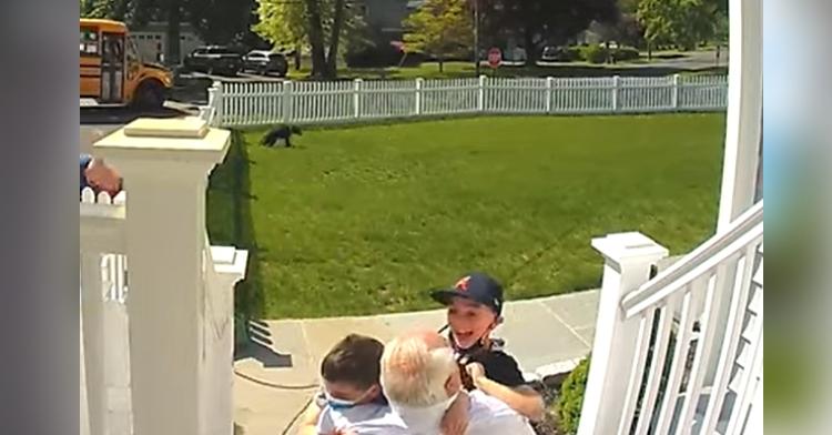 two boys hugging grandpa on porch