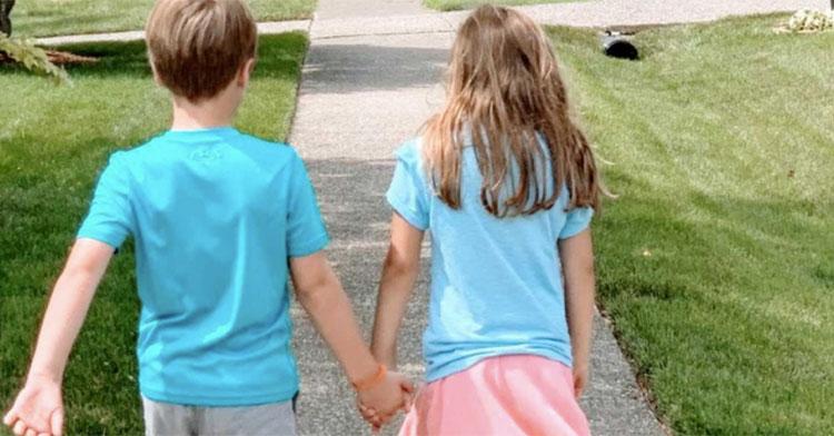 little boy in blue shirt holding hands with little girl in blue shirt