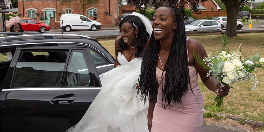 bride standing next to bridesmaid outside of black car
