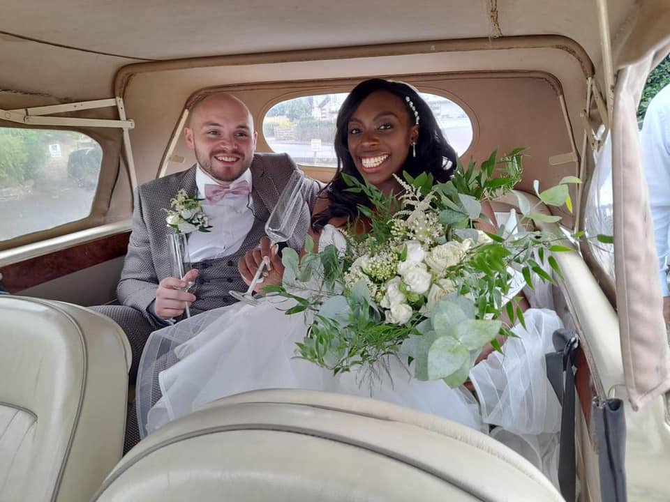 groom and bride smiling in car