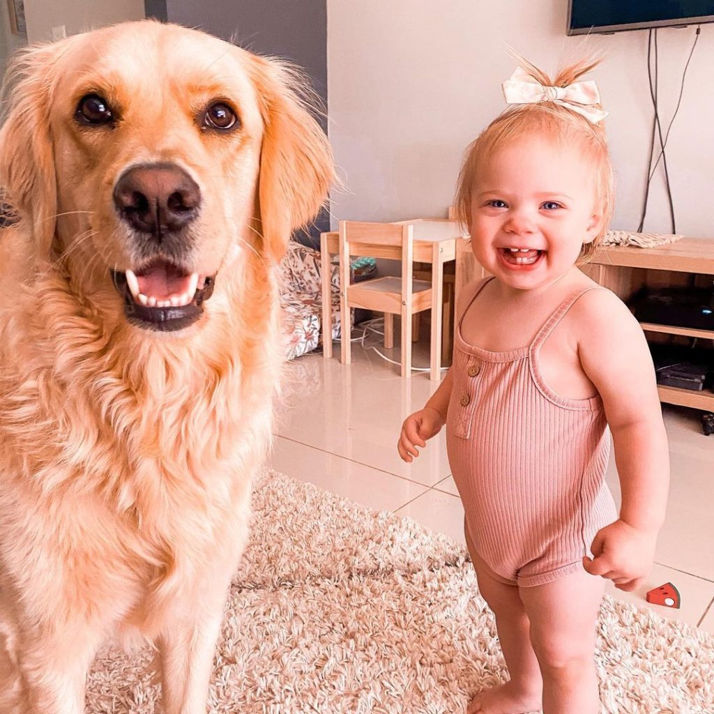 baby and golden retriever smiling