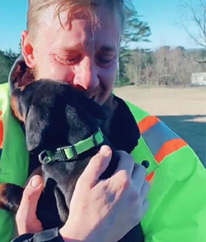 man crying tears of joy while holding dog