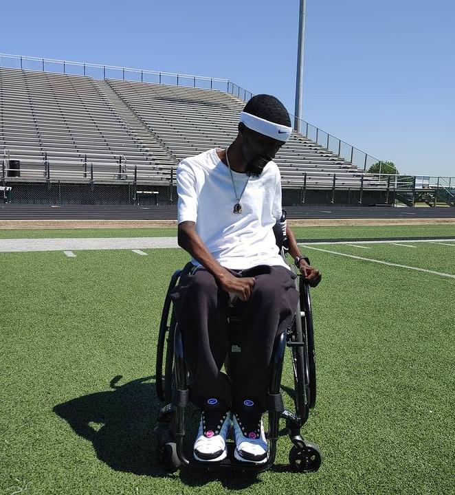 man sitting in wheelchair on football field