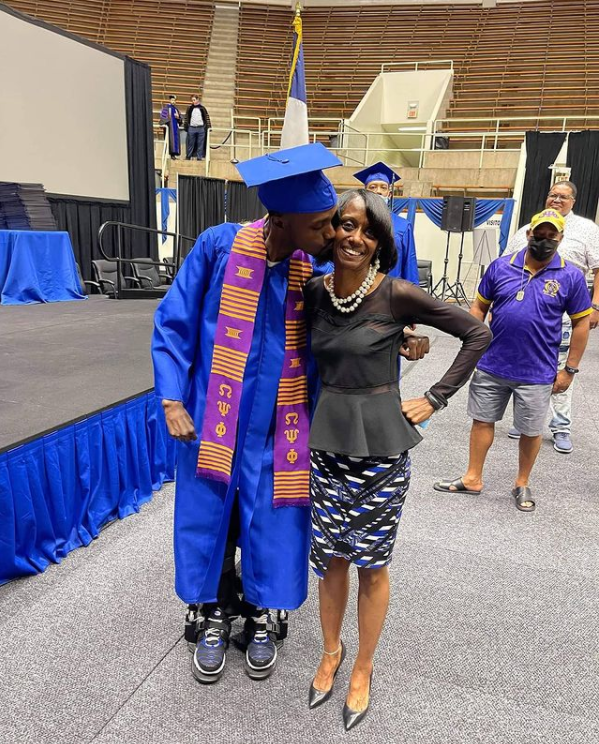 man in graduation cap and gown kissing woman on cheek