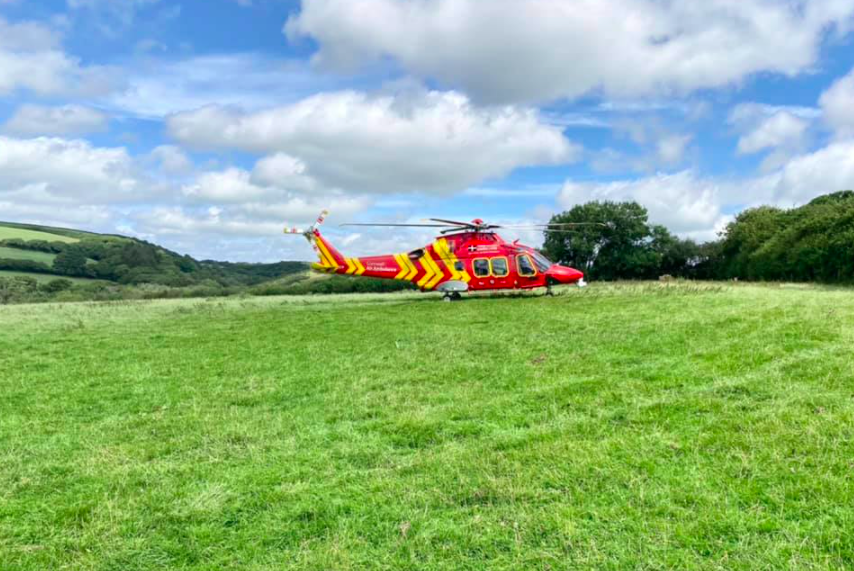 red and yellow helicopter in grassy field