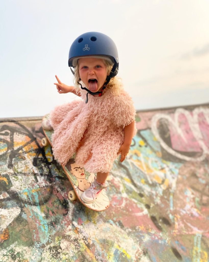 4-year-old skateboarding wearing a pink dress and a blue helmet
