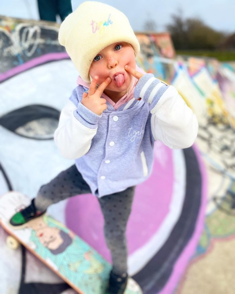 toddler skateboarder sticking her tongue out