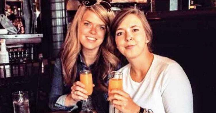 sisters at restaurant holding glasses