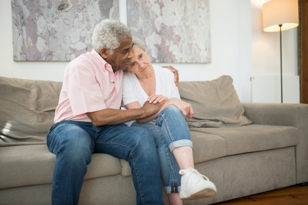 man comforting a woman while they sit on a couch