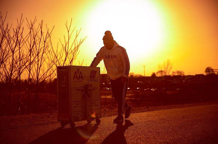 man pushing cart in sunset