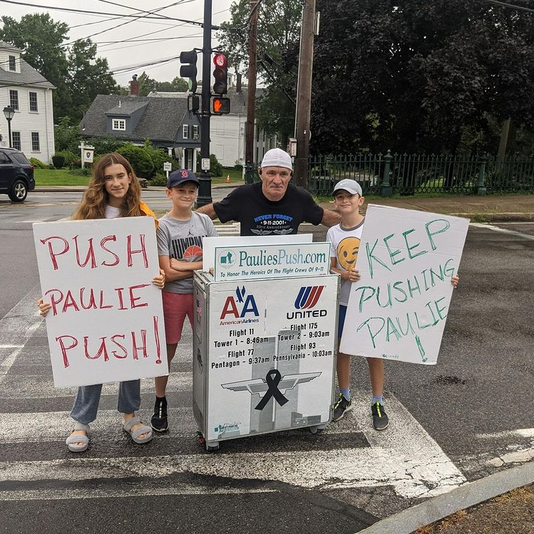 man posing with children holding signs