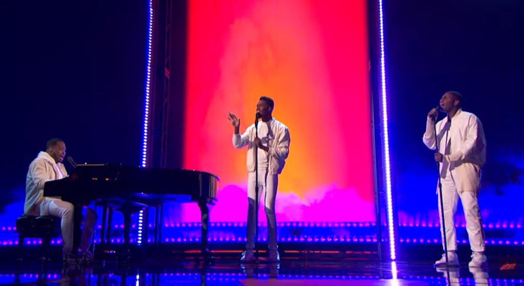 "three men singing on ""america's got talent"" stage"