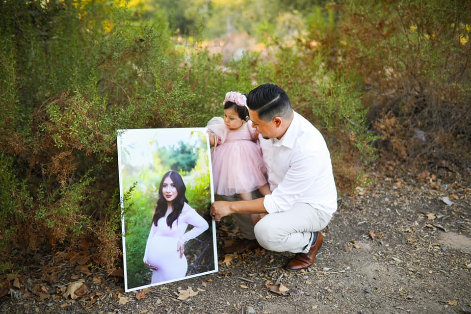 dad and baby daughter crouched next to portrait of pregnant mom