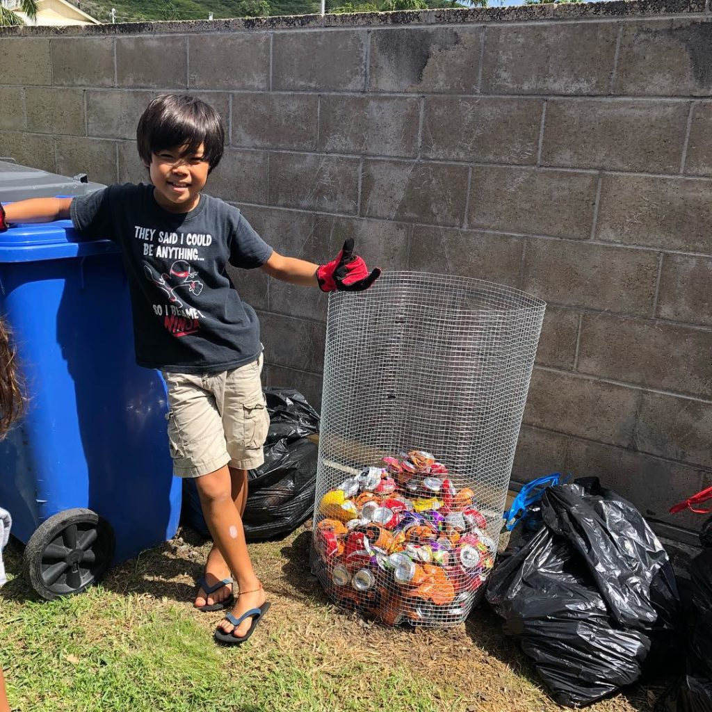 boy smiling next to a recycling container