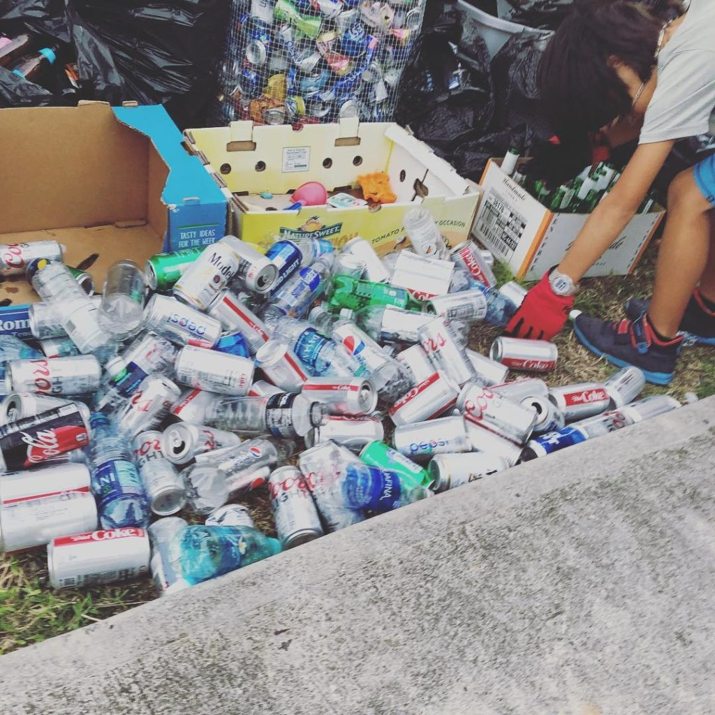 boy collecting cans and bottles from large pile
