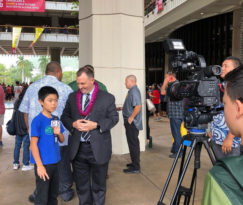 little boy being interviewed by a man from the news