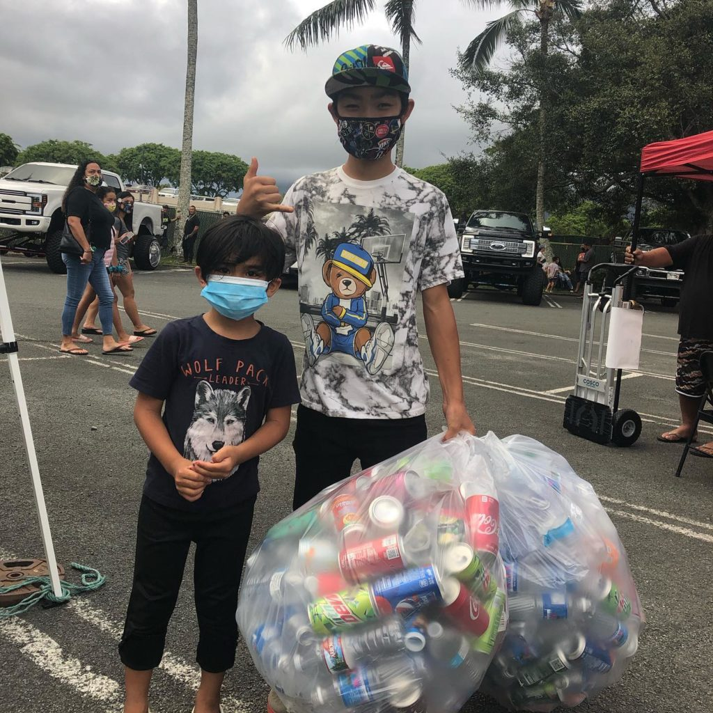 teen and boy pose outiside with a giant bag of recycling