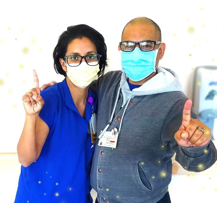 woman and man wearing medical masks and holding up their index fingers