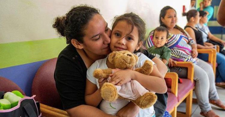 mom hugging daughter holding teddy bear in health clinic