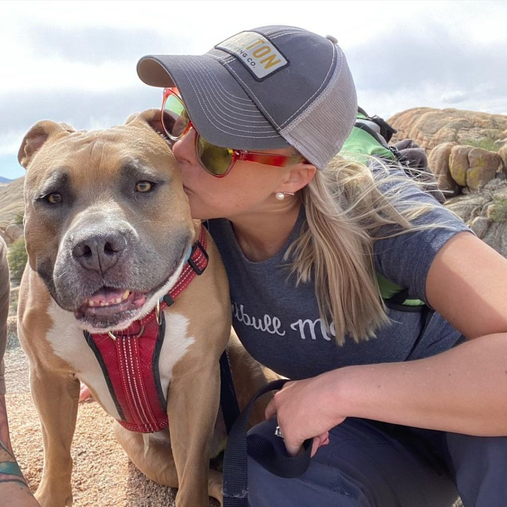 woman kissing happy pit bull on hike