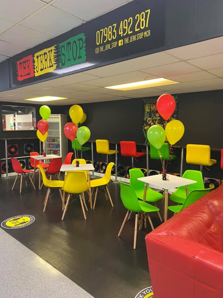 red, yellow, and green dining tables and chairs under sign that reads The Jerk Stop