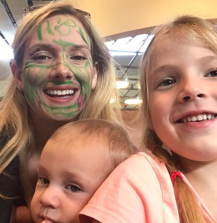 woman with face covered in maker smiling with two children