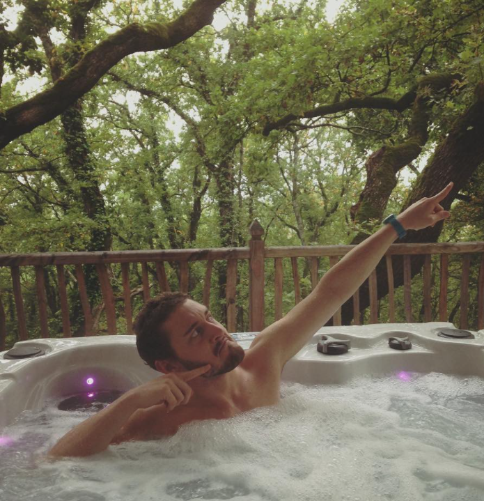 man pointing up at the sky while in a hot tub