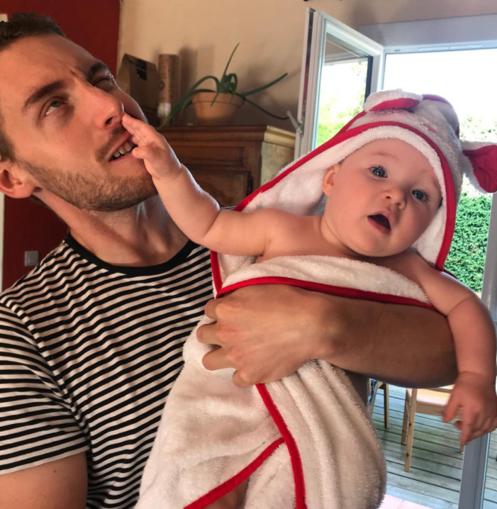 man struggling to hold baby