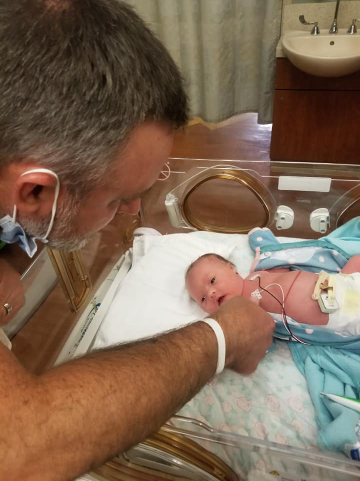 man reaching toward new born baby in hospital