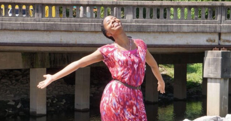 woman smiling in pink dress with her arms stretched wide