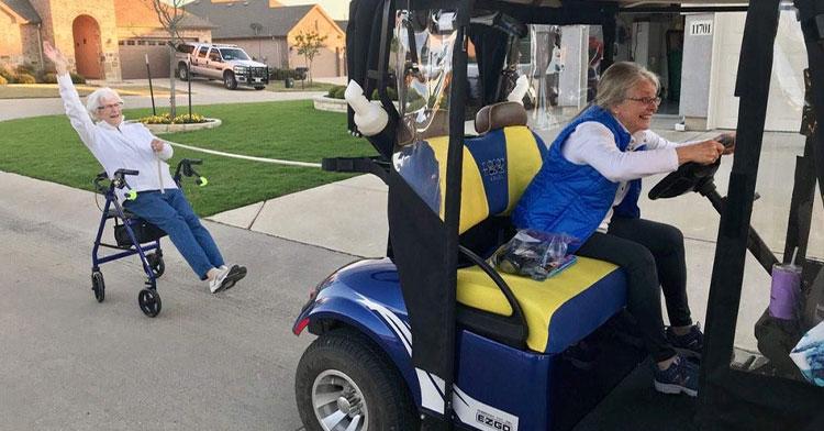 grandma in golf cart pulling grandma on rolling chair behind her