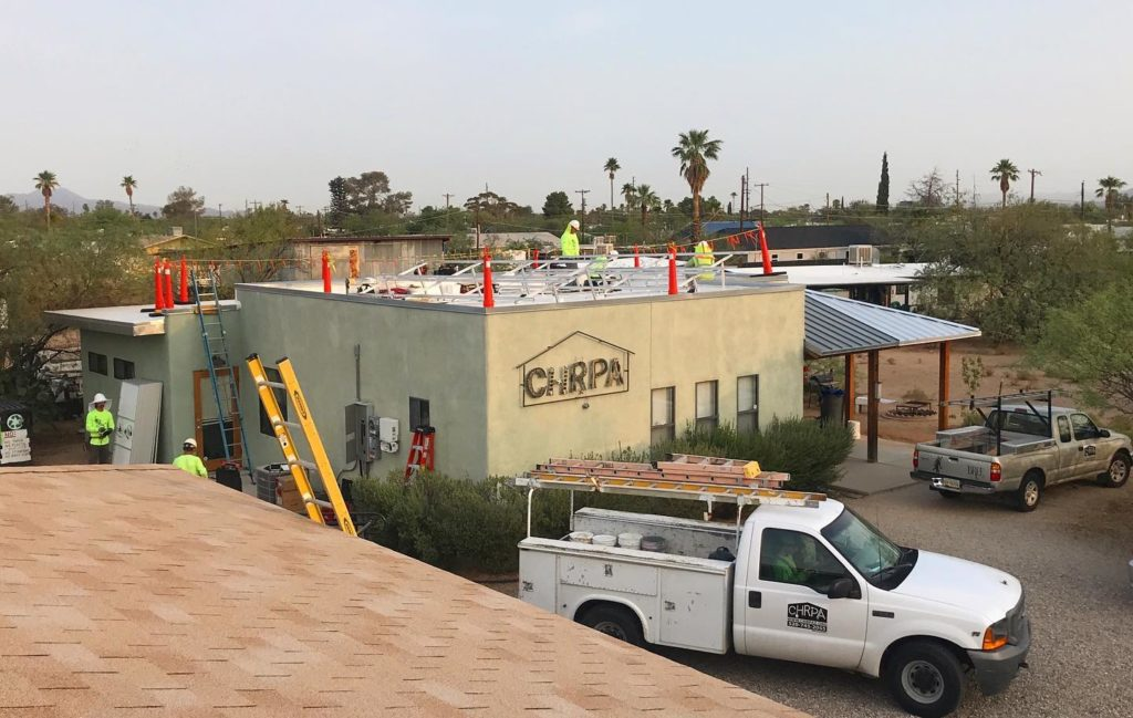 construction workers on building with CHRPA logo on outside