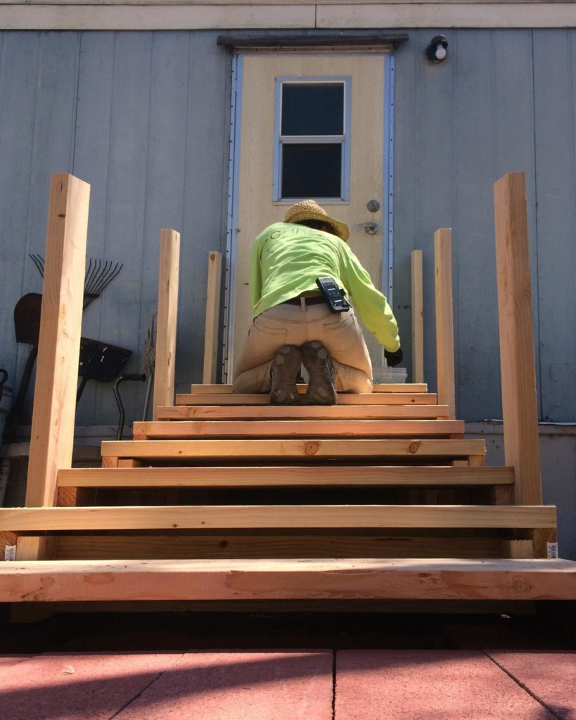 man working on wooden staircase leading up to home