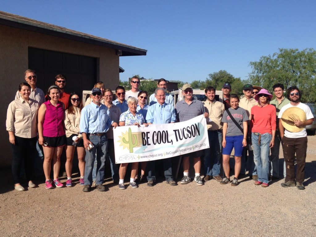 people standing outside home with sign that reads be cool, tucson