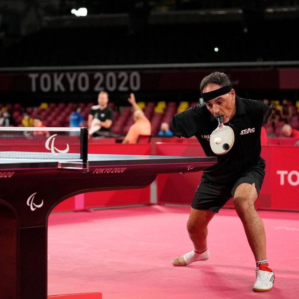 man with no arms holding table tennis racket in his mouth