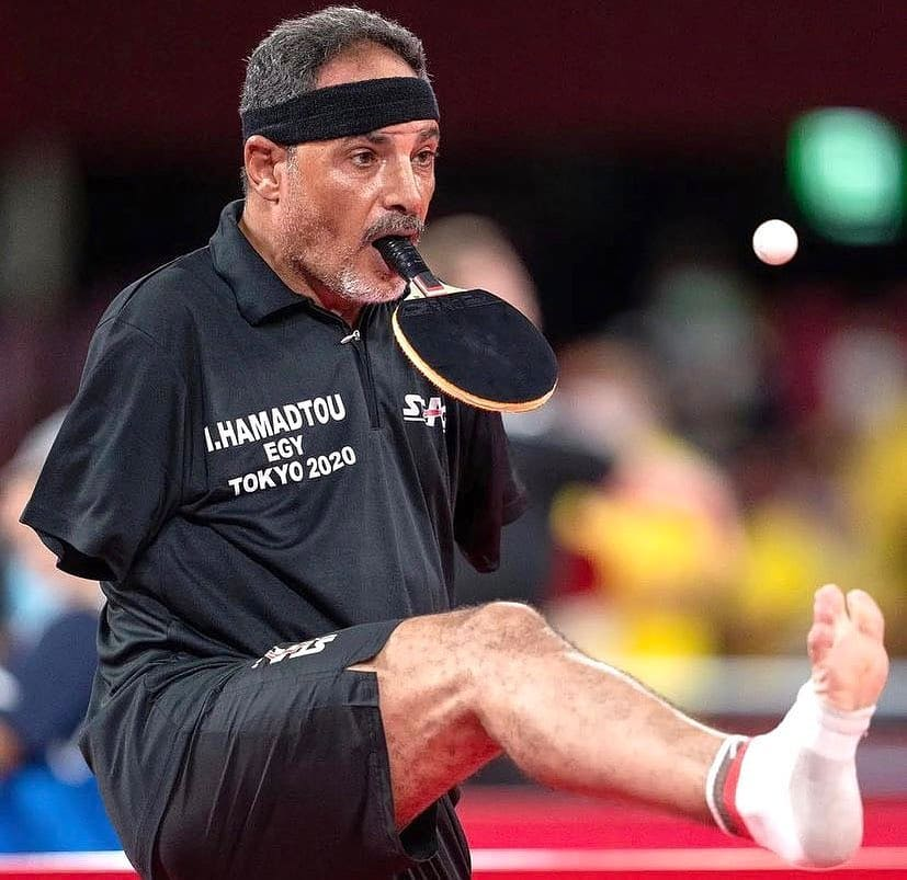 table tennis player with no arms holding racket in his mouth with one leg in the air