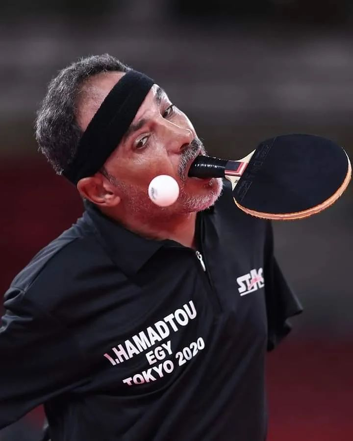 man with no arms holding table tennis paddle in mouth and wearing black shirt and sweat band
