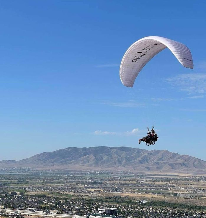 person paragliding with sky and mountain in background