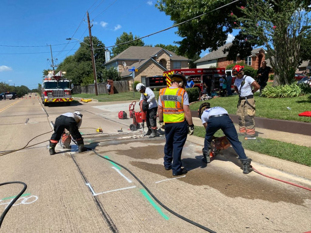 firemen cutting their way into the ground to save dog