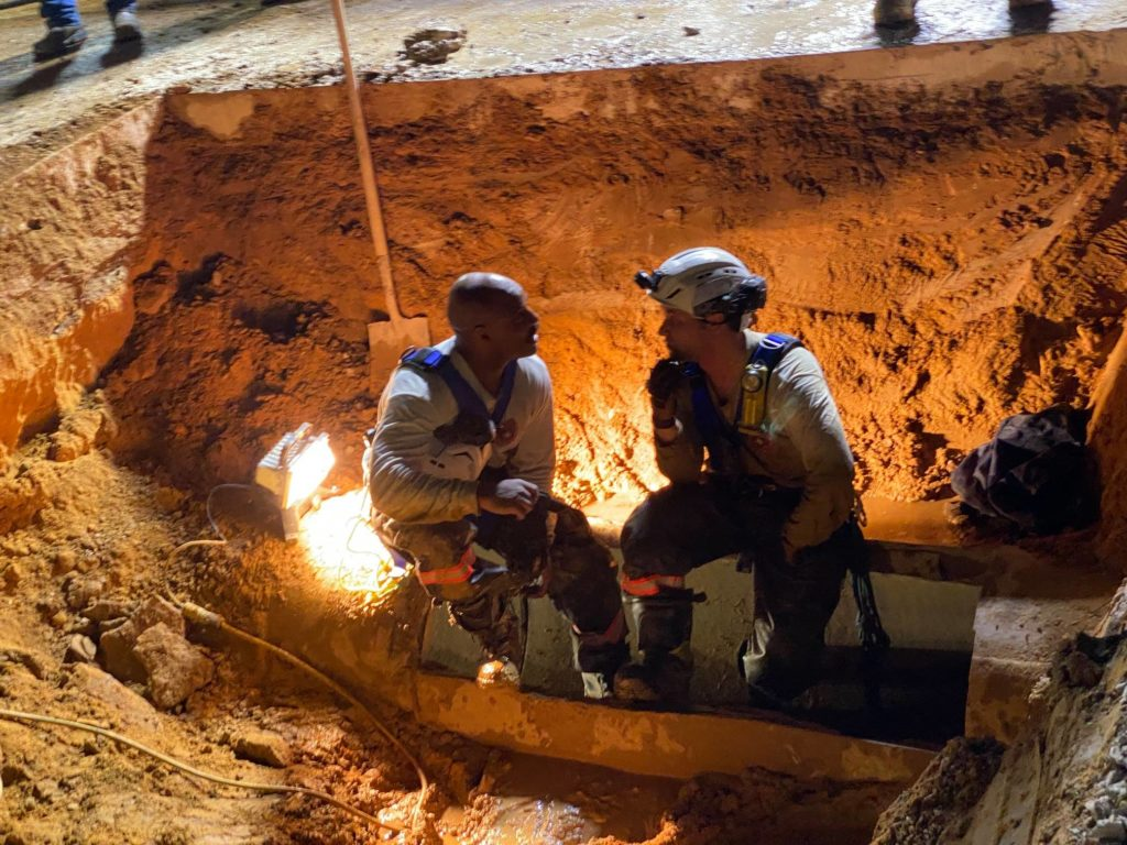 firemen sitting and talking on storm drain