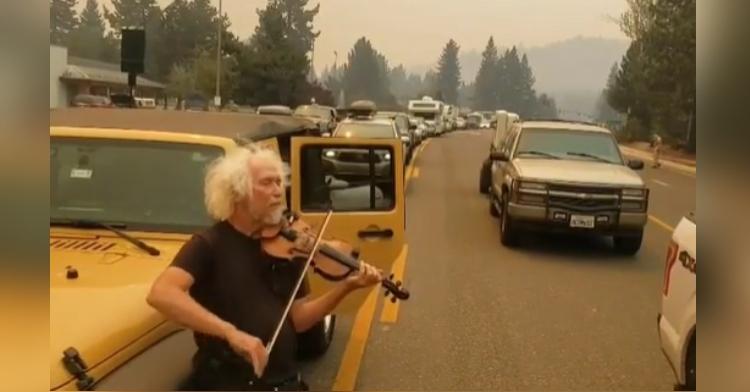 man plays violin on gridlocked highway