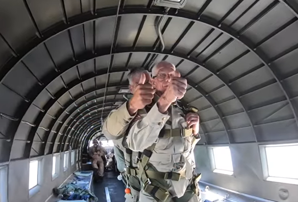 100-year-old holding thumb up in plane with tandem jumper behind him