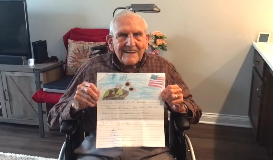 old man in wheelchair smiling while holding up a letter
