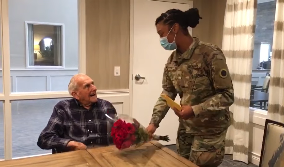 old man in wheelchair smiling up at woman in face mask and army uniform