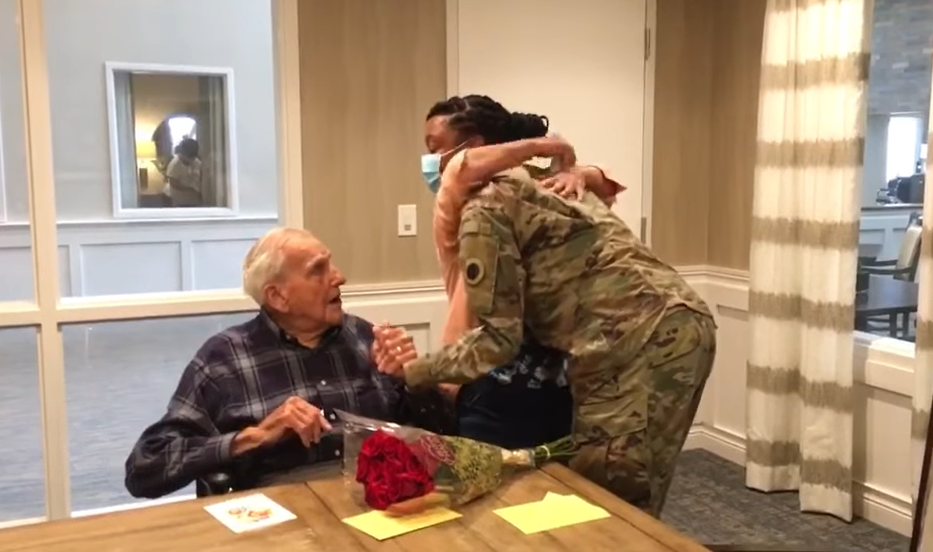 two women hugging while old man in wheelchair holds one of their hands