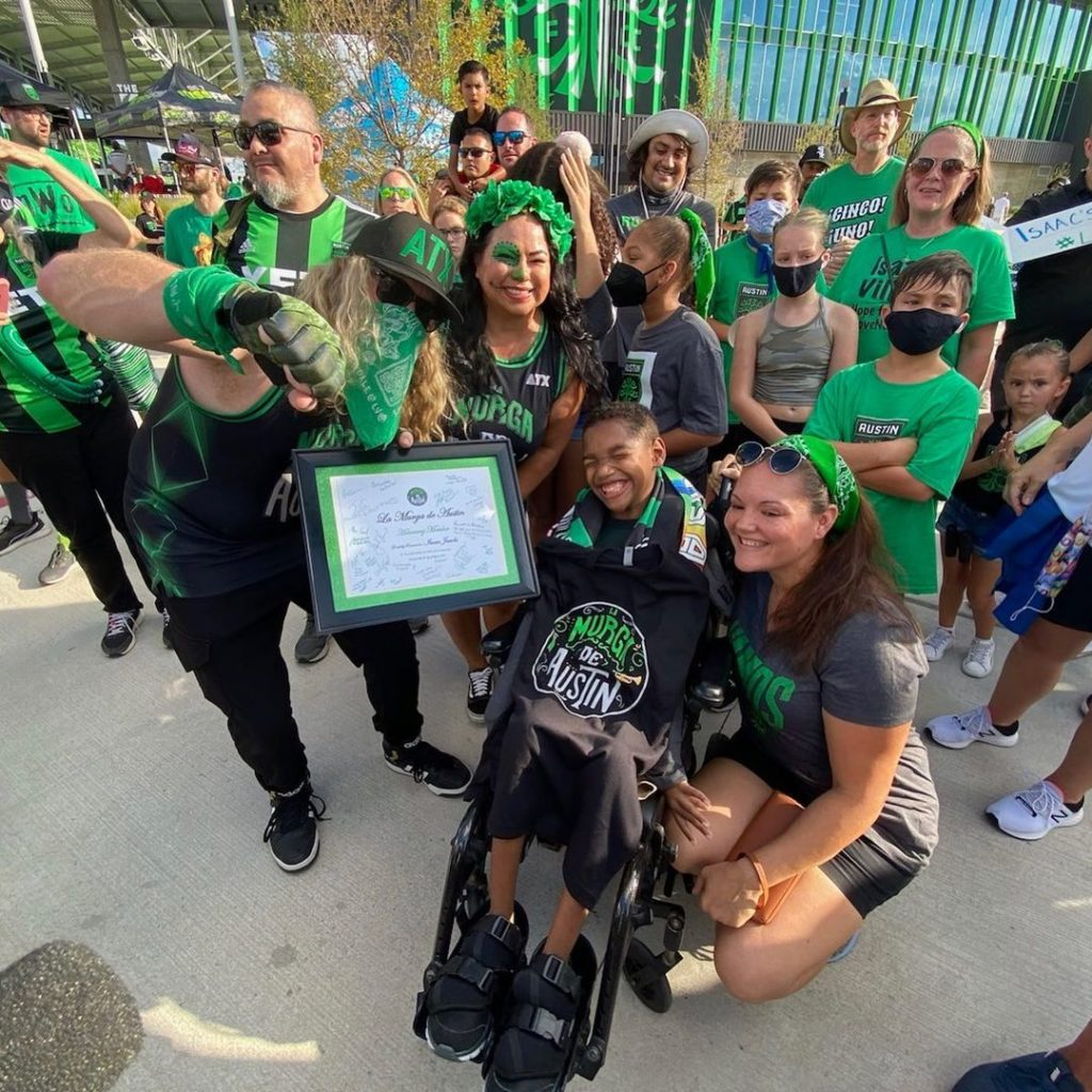 marching band smiling around teen in wheelchair
