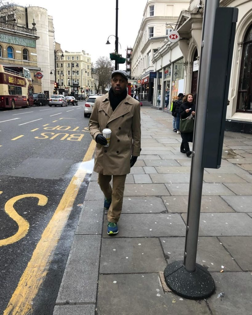 man walking down street in cold weather gear holding cup of coffee