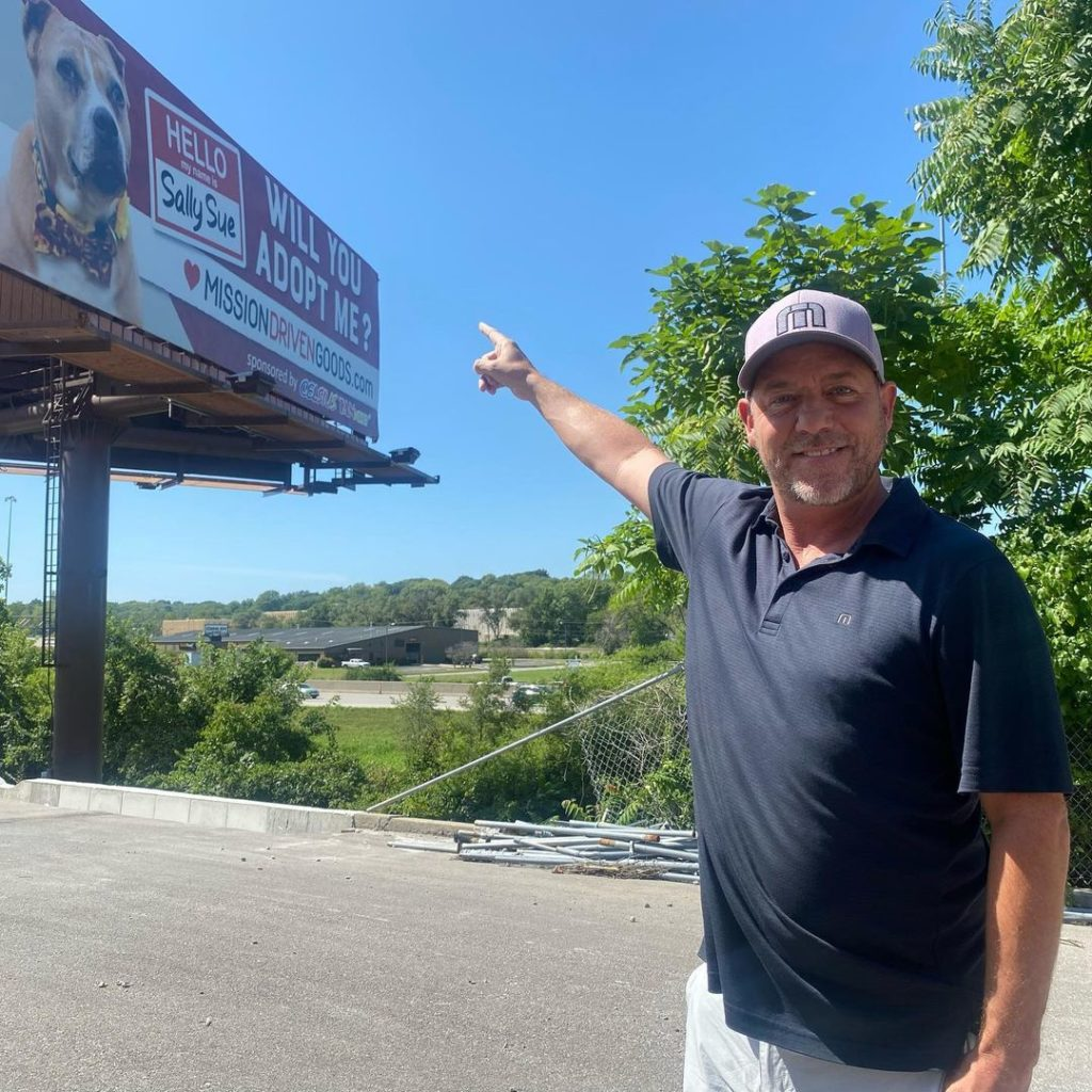 man pointing at billboard with adoptable dog on it