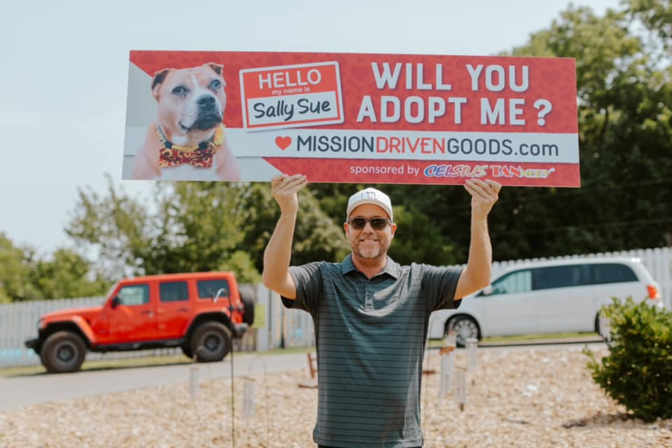 man holding sign with dog adoption info