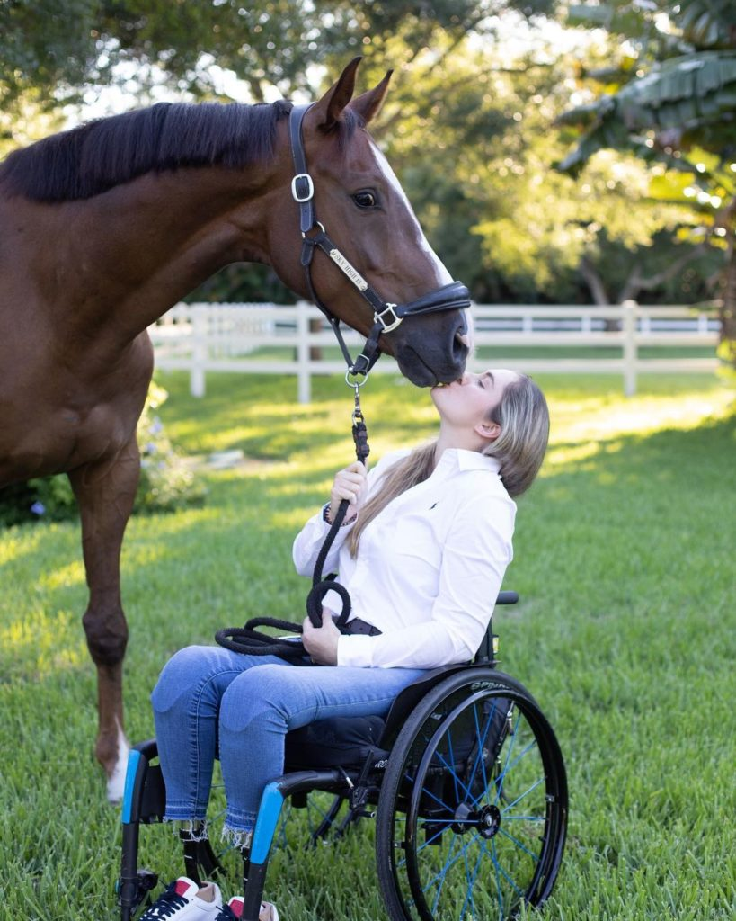woman in wheelchair kissing horse's nose